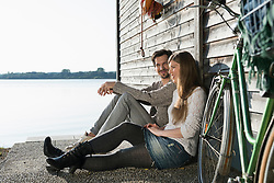Young couple sitting relaxing lake boathouse