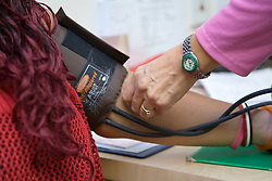Midwife taking a pregnant woman's blood pressure,