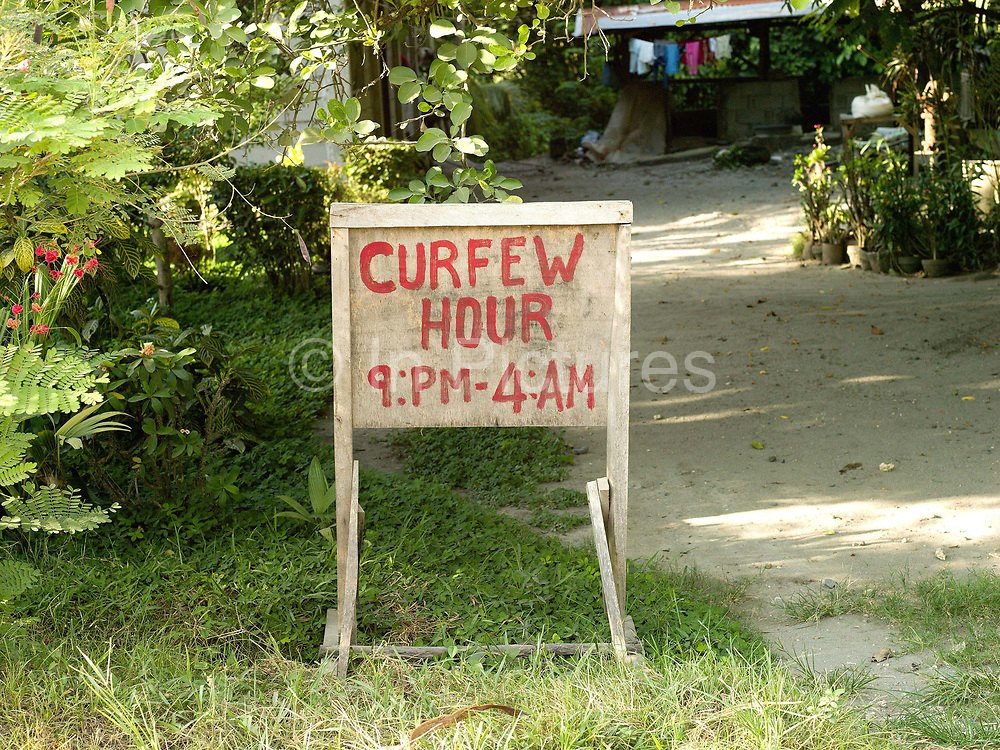 Curfew sign near Esperanza, Sultan Kudarat province, The Philippines. Muslim separatism and communist insurgency have claimed the lives of an estimated 120,000 people and have displaced about two million more civilians over the last four decades. Because of the instabilities, local communities in Mindanao have some of the highest degree of exposure to violence and suffered acute poverty, food insecurity and lack of basic social services.