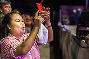 22 NOVEMBER 2013 - BANGKOK, THAILAND: A spectator at a Prathom Bunteung Silp mor lam show uses her smart phone to photograph a performer.  Mor Lam is a traditional Lao form of song in Laos and Isan (northeast Thailand). It is sometimes compared to American country music, song usually revolve around unrequited love, mor lam and the complexities of rural life. Mor Lam shows are an important part of festivals and fairs in rural Thailand. Mor lam has become very popular in Isan migrant communities in Bangkok. Once performed by bands and singers, live performances are now spectacles, involving several singers, a dance troupe and comedians. The dancers (or hang khreuang) in particular often wear fancy costumes, and singers go through several costume changes in the course of a performance. Prathom Bunteung Silp is one of the best known Mor Lam troupes in Thailand with more than 250 performers and a total crew of almost 300 people. The troupe has been performing for more 55 years. It forms every August and performs through June then breaks for the rainy season.     PHOTO BY JACK KURTZ
