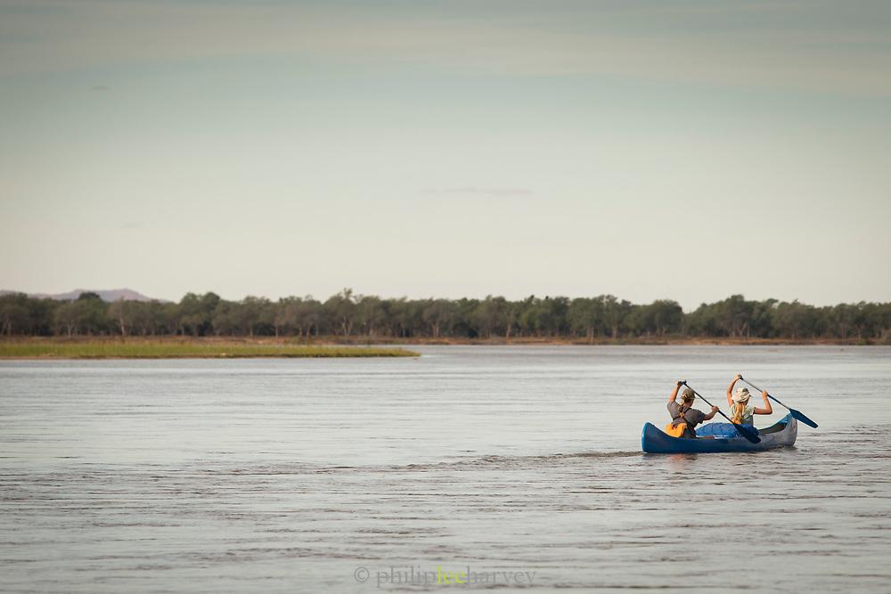 Two people in canoe with paddles, Zambezi River, Zambia