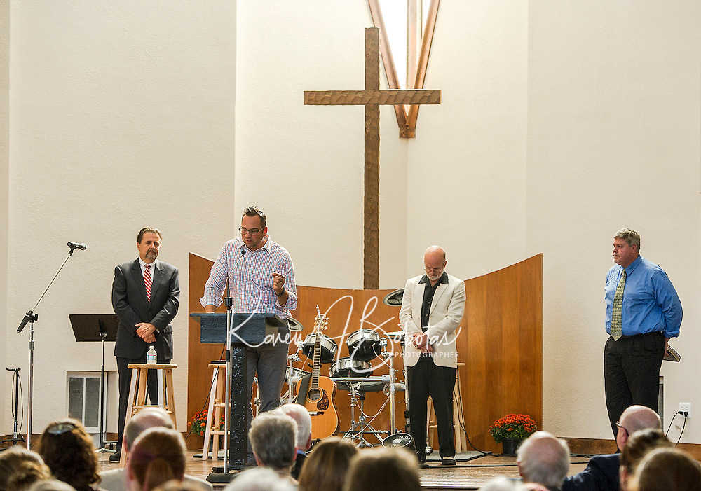 Mayor Edward Engler, Pastor Mark Warren of Grace Captial Church(at podium), Past Dick AuCoin of the Lakes Region Vineyard Church and Pastor Glen Carter of the Hope Community Chapel address parishoners and guests during the dedication ceremonty on Sunday afternoon.   (Karen Bobotas/for the Laconia Daily Sun)