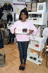 SINITTA with pairs of male & female baby shoes at the Plusher Fair, Lindley Hall, Royal Horticultural Halls, Vincent Square, London, on 9th November 2013.