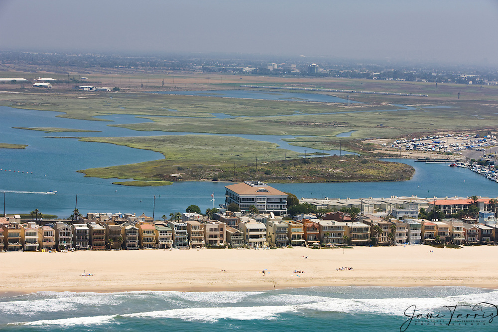 An aerial view of beach houses sitting on a strand between the Bolsa Chica wetlands and the Pacific Ocean beach, Sunset Beach,California, USA