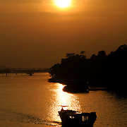 In the late afternoon, a boat is silhoutted against the golden sunset on the Perfume River in Hue, Vietnam.