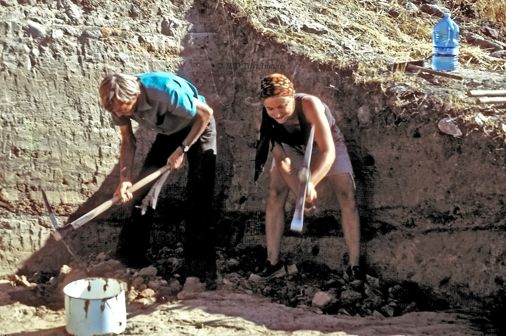 Archaeology can be hard labor.  Here two workers, a man and a young woman, each dig down to the next layer of a trench, each using a pickaxe.  A bucket for any finds is in front of them, and a half gallon bottle of water stands at the edge of the trench.  It is very hot in the sun.