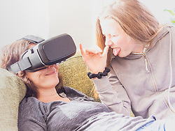 Mischievous girl with mother using virtual reality headset