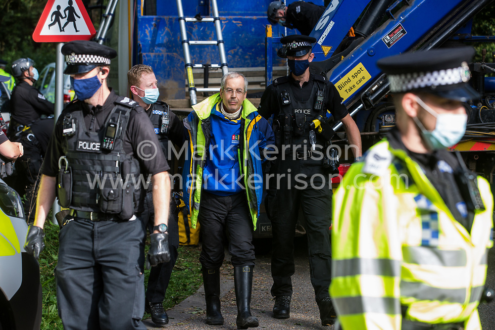 Thames Valley Police officers arrest one of two anti-HS2 activists who had occupied the roof of the cab of a HGV in order to block its passage to works for the HS2 high-speed rail link on 28 September 2020 in Denham, United Kingdom. Environmental activists continue to try to prevent or delay works on the controversial £106bn project for which the construction phase was announced on 4th September from a series of protection camps based along the route of the line between London and Birmingham.