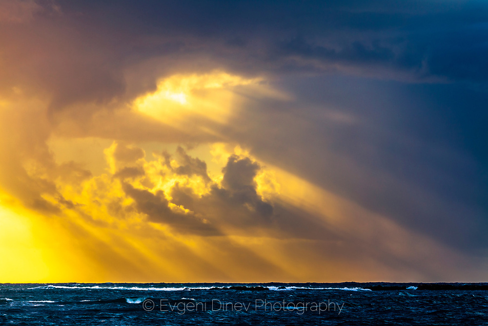 Sun rays from the sky over the sea at sunset