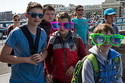 A group of young male students on a tourist trip across Tower bridge wearing oversized sunglasses. Tower Bridge, London. 5th May 2016