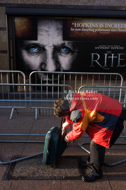 The actor Anthony Hopkins stares from a movie poster while a passer-by bends by his wheelie luggage.