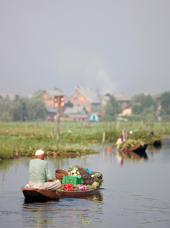 People paddling their shikara, a local wooden boat, with goods to sell at the floating market in Srinigar, Kashmir, India