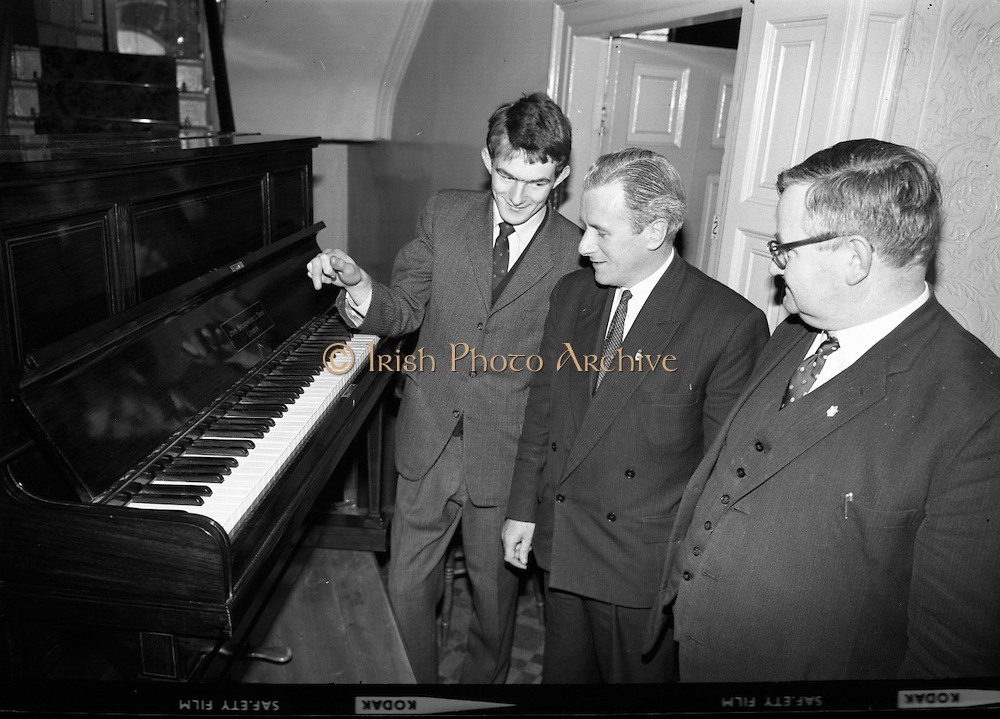 "Messrs. Pigott and Co. Ltd, handed over a piano to a group of students, calling themselves ""The Hooligans"".  The students will push the piano to Cork, with the boys playing it on route and collecting on behalf of old age pensioners. Picture shows Mr. Michael Tobin, Pigott and Co., handing over the piano to be pushed to the leader of the students, Dan Cullinane, at 62 Lower Mount Street.  Included is Mr. W.J. Martin, organiser of the group..14.03.1964"