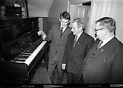 """Messrs. Pigott and Co. Ltd, handed over a piano to a group of students, calling themselves """"The Hooligans"""".  The students will push the piano to Cork, with the boys playing it on route and collecting on behalf of old age pensioners. Picture shows Mr. Michael Tobin, Pigott and Co., handing over the piano to be pushed to the leader of the students, Dan Cullinane, at 62 Lower Mount Street.  Included is Mr. W.J. Martin, organiser of the group..14.03.1964"""