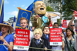 "© Licensed to London News Pictures. 20/07/2019. London, UK. A stilts-walker wearing a giant NIGEL FARAGE'S<br /> head pulls two puppets, the Conservative leadership candidates BORIS JOHNSON and JEREMY HUNT during the ""No to Boris. Yes to Europe"" march in central London. Photo credit: Dinendra Haria/LNP"