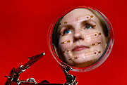 """Portrait of UIC College of Engineering BioE undergraduate student Amanda Bogseth reflected in a silicon wafer """"master"""" dish with microfluidic designs made for the application of cell cycle synchronization in Chicago"""