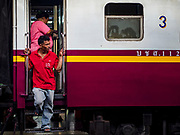 11 APRIL 2018 - BANGKOK, THAILAND:  A man stands in the door of a departing train at Hua Lamphong train station in Bangkok. Songkran is the traditional Thai New Year and is one of the busiest travel periods of the year as Thais leave the capital and go back to their home provinces or resorts in tourist areas.      PHOTO BY JACK KURTZ