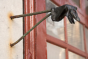 a in the street lost glove hanging from a from the wall protruding metal hook