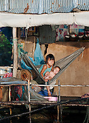 A young girl holing a baby in a floating village community on the great Tonlé Sap lake, Cambodia