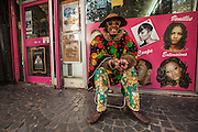 FRANCE. Paris, Ile-de-France. October 29th, 2013. An eccentrically dressed man sits outside a local coiffure (hairdresser), promoting their services to local residents in the 11th arrondissement.