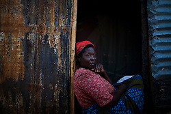 A woman sits in the doorway of her shelter, made of a tarp and corrugated tin, at an IDP camp in Burnt Forest. Four months election violence erupted in Kenya there are still some 300,000 people displaced, half of which are living in IDP camps. The violence was centered in the Rift Valley, Kenya's fertile bread basket.  Due to the violence and displacement many Kenya farmers have been unable to work their land for 4 months, leading to worries that Kenya will face severe food shortages by the end of the year.