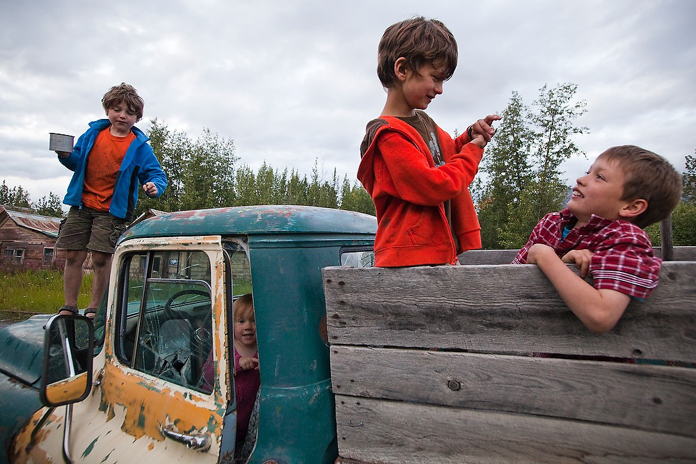 Children play in one of the many old abandoned trucks scattered around the town of McCarthy, Alaska.