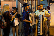 Male and female Brazilian Gaucho musicians and production team backstage, talking and playing instruments, practicing before the show at Reponte da Cancao music festival and song competition in Sao Lorenzo do Sul, RIo Grande do Sul, Brazil.