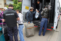 © Licensed to London News Pictures. 26/06/2013 London, UK. Romanian immigrants are driven to the airport  and served eviction papers after a dawn raid on Hendon Football Club, Hendon North West London. The 68 illegal immigrants were removed in a joint Home Office Immigration, Met Police and homeless charity operation after the site has been occupied for more than 2 years.<br /> Photo credit : Simon Jacobs/LNP