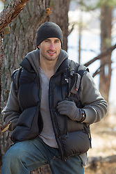 handsome rugged man outdoors in the wintertime by a tree