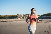 Woman in her twenties running as part of a workout during an early morning on the beach in Newport, Rhode Island