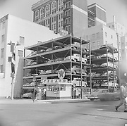 9722-26-1.  Elevated parking garage. Pidgeon (sic) Hole Parking, at its original location at 801 SW Stark. The view is looking northeast to the the corner of SW 9th & Stark. The structure extends the full block down to SW Park. This picture was taken in the summer of 1954, before the entire structure was moved two blocks south to 820 SW Alder in the mid-1950's. The mis-spelling of Pigeon was the least of their problems, the reason they went out of business is because the unreliable elevator marooned customer's cars on the upper levels until repairs could be completed. The lot included a Texaco Gas Station. (source: license plate is 1954, city directory searches, interview with Dave Hite who worked there when they went out of business)