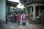 Irine, at right, stands next to her rental home, left, with her 25-year-old daughter, Leticia, in Gulu. Irine was abducted by LRA forces in the middle of the night when she was about 13 years old at St. Mary's school and was assigned to a commander six months later. She became the 7th wife and gave birth to Leticia. She works as a building painter now.