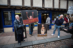 © Licensed to London News Pictures . 19/11/2014 . Kent , UK . A portrait of Nigel Farage by political artist Kaya Mar , held up by a UKIP activist , outside the UKIP shop , on Market Street , Rochester , this morning (19th November 2014) . The Rochester and Strood by-election campaign following the defection of sitting MP Mark Reckless from Conservative to UKIP . Photo credit : Joel Goodman/LNP