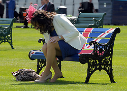 © Licensed to London News Pictures. 19/06/2012. Ascot, UK  A woman changes her shoes on a bench painted with a Union Flag. Day one at Royal Ascot 19 June 2012. Royal Ascot has established itself as a national institution and the centrepiece of the British social calendar as well as being a stage for the best racehorses in the world.. Photo credit : Stephen Simpson/LNP