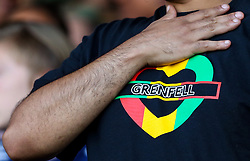 2 September 2017 - Charity Football - Game 4 Grenfell - A man wearing a Grenfell t-shirt in Rastafarian colours holds his hand over his chest - Photo: Charlotte Wilson