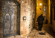 A jewish man passes by a bronze door while walking back home in one of the narrow alleys of Jerusalem Old City.
