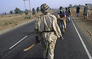 Dressed in flamboant clothes, Husa Hunter gangs play powergames and ritual ceremonies, the control the rural villages, as ghetto gangs control urban areas...The implementation of Islamic Sharia Law across the twelve northern states of Nigeria, centres upon Kano, the largest Muslim Husa city, under the feudal, political and economic rule of the Emir of Kano. Islamic Sharia Law is enforced by official state apparatus including military and police, Islamic schools and education, plus various volunteer Militia groups supported financially and politically by the Emir and other business and political bodies. Fanatical Islamic Sharia religious traditions  are enforced by the Hispah Sharia police. Deliquancy is controlled by the Vigilantes volunteer Militia. Activities such as Animist Pagan Voodoo ceremonies, playing music, drinking and gambling, normally outlawed under Sharia law exist as many parts of the rural and urban areas are controlled by local Mafia, ghetto gangs and rural hunters. The fight for control is never ending between the Emir, government forces, the Mafia and independent militias and gangs. This is fueled by rising petrol costs, and that 70% of the population live below the poverty line. Kano, Kano State, Northern Nigeria, Africa