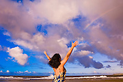 Rainbow over woman raising arms on Tunnels Beach at sunset, Island of Kauai, Hawaii