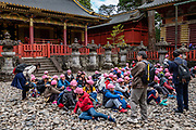 """School kids group. Toshogu Shrine is the final resting place of Tokugawa Ieyasu, the founder of the Tokugawa Shogunate that ruled Japan for over 250 years until 1868. Ieyasu is enshrined at Toshogu as the deity Tosho Daigongen, """"Great Deity of the East Shining Light"""". Initially a relatively simple mausoleum, Toshogu was enlarged into the spectacular complex seen today by Ieyasu's grandson Iemitsu during the first half of the 1600s. The lavishly decorated shrine complex consists of more than a dozen buildings set in a beautiful forest. Countless wood carvings and large amounts of gold leaf were used to decorate the buildings in a way not seen elsewhere in Japan. Toshogu contains both Shinto and Buddhist elements, as was common until the Meiji Period when Shinto was deliberately separated from Buddhism. Toshogu is part of Shrines and Temples of Nikko UNESCO World Heritage site."""