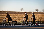 Amish children ride push scooters to church during sunrise in Bird in Hand, PA.
