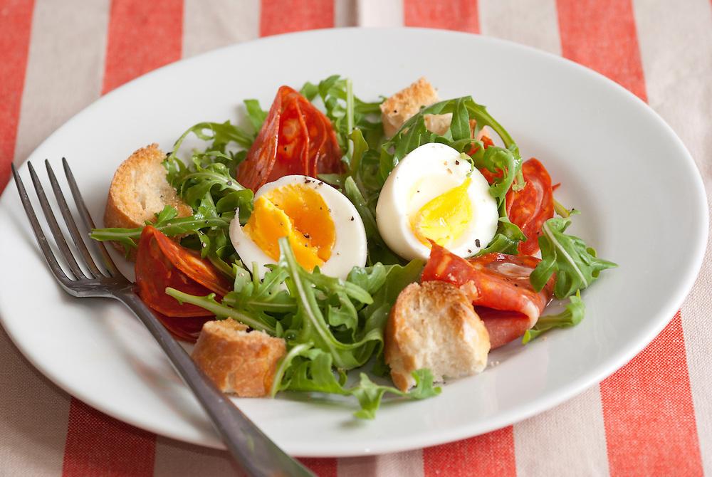 Soft-boiled egg, chorizo and rocket salad on a plate