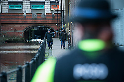 "© Licensed to London News Pictures . Manchester , UK . FILE PICTURE DATED 29/12/2013 of a PCSO standing behind police tape adjacent to the River Medlock off Oxford Road in Manchester City Centre as two officers search the footpath adjacent to the canal . The search for a 17 year old from Stockport , who was last seen in the early hours of Saturday 28th December in Manchester City Centre following a night out with friends . Greater Manchester Police have issued a statement after suggestions that a number of deaths in and around Manchester's canals may be linked to a serial killer , named in local folklore as "" The Pusher "" . The statement said "" Absolutely no evidence whatsoever of foul play has been established "" . Photo credit : Joel Goodman/LNP"