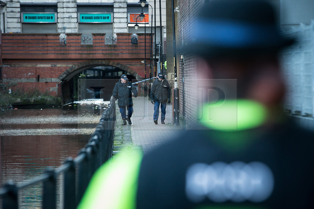 """© Licensed to London News Pictures . Manchester , UK . FILE PICTURE DATED 29/12/2013 of a PCSO standing behind police tape adjacent to the River Medlock off Oxford Road in Manchester City Centre as two officers search the footpath adjacent to the canal . The search for a 17 year old from Stockport , who was last seen in the early hours of Saturday 28th December in Manchester City Centre following a night out with friends . Greater Manchester Police have issued a statement after suggestions that a number of deaths in and around Manchester's canals may be linked to a serial killer , named in local folklore as """" The Pusher """" . The statement said """" Absolutely no evidence whatsoever of foul play has been established """" . Photo credit : Joel Goodman/LNP"""