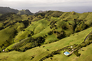 """Drone view of Saint Helena Island<br /> <br /> St. Helena island, part of the British Overseas Territory, measures just 6 by 10 miles and comprises 47 square miles of rocky coastline, colored desert, rippled pastureland and lush cloud forest. This speck of land is one of the most remote islands on earth.<br /> <br /> Since discovery in 1502, until the start of commercial flights in October 2017, the sea route had been the only way to reach St Helena. At its peak more than 1,000 ships a year visited on the way to and from India and the Far East via the Cape of Good Hope. That declined after 1869 with the opening of the Suez Canal.<br /> <br /> The age of the airplane bypassed St. Helena because it offered no flat land for a runway and was consistently buffeted by treacherous winds sweeping off the water. But in the hope of stoking the tourist trade, the British spent almost $400 million to fill in a valley by 2014 with some 800 million pounds of dirt and rock to solve the runway problem and build an airport. Today, only a special, stripped-down Embraer 190 jet with the best pilots in the world can stick the landing. The airport was, soon after, dubbed as the """"world's most useless airport"""" due to high winds and difficult landings. <br /> <br /> St. Helena is a volcanic outcrop and its varying nature from semi-arid desert to jungle, to rolling green hills, is beautiful. The wildlife is unique: you can swim with docile whale sharks, watch the endemic ire Bird and visit Jonathan, the 187-year-old tortoise, the world's oldest-recorded living land animal, who since the new year has had his own Twitter account (@Jonathan_onStH)."""