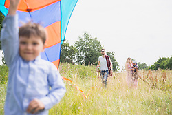 Family walking on meadow with picnic basket and kite in the countryside, Bavaria, Germany