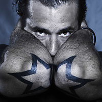 studio shot portrait of a urban stylish man with stars tattoos on his elbows