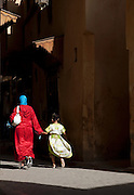 A mother and daughter walk in the narrow streets of the medina in Fes, Morocco