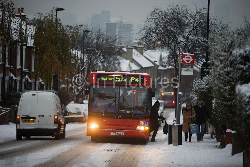 A P4 bus service destination Lewisham Station climbs Herne Hill early after fresh overnight snowfall in the south London area. During a mid-winter morning, when commuters are struggling to reach their work places, the capital also finds it hard for transport and infrastructure to keep running as normal. With its headlights on half-beam, the snow is still making this hill treacherous to climb as this heavy vehicle again starts from the bus stop, having lost its traction on the slippery road surface. A passenger alights, carefully stepping down from the bus onto the snowy kerb as other people walk uphill, preferring to make their own way. The snow rests on surrounding Victorian house roofs and in the distance; it is a bleak day in the misty urban light where high-rise flats (apartments) can be seen.