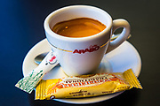 A cup of espresso, sugar and a biscotti