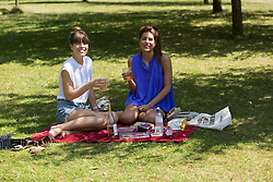 © Licensed to London News Pictures. 22/07/2014. London, UK. Two young women enjoying a picnic in the sunshine in St Regents Park in central London this lunchtime. Photo credit : Vickie Flores/LNP